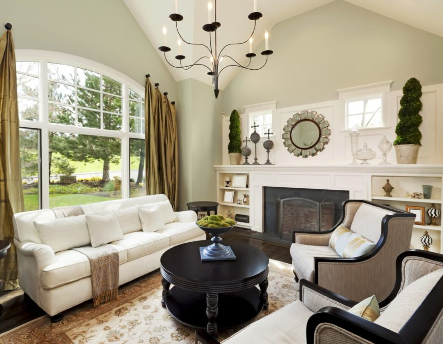 A small living space featuring a white couch and a round center table along with a fireplace, lighted by a gorgeous chandelier.