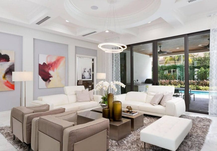 A contemporary living space featuring a stunning white ceiling along with beautiful walls and wall decors. The white sofa set looks perfect with the room too.