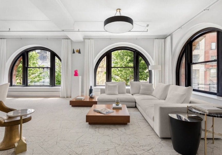 Large living room featuring a white sofa set along with a stylish flooring and a white ceiling.