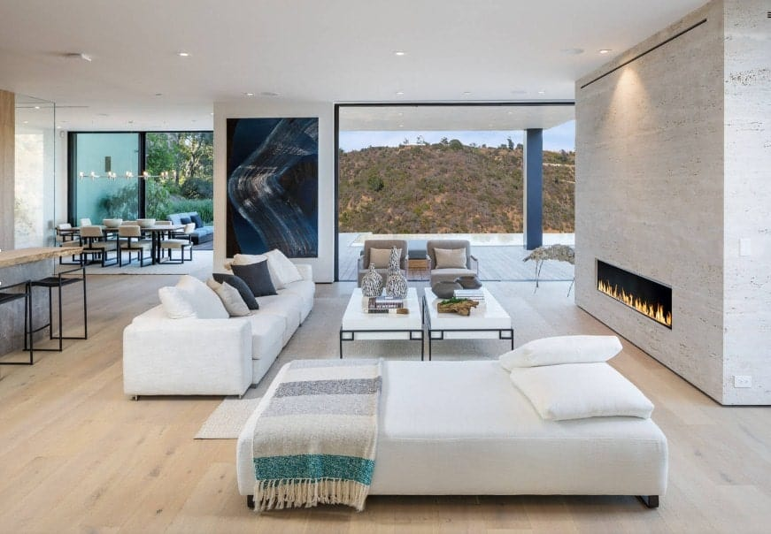 A great room featuring a spacious living area featuring a white couch and two white center table along with a gas fireplace.