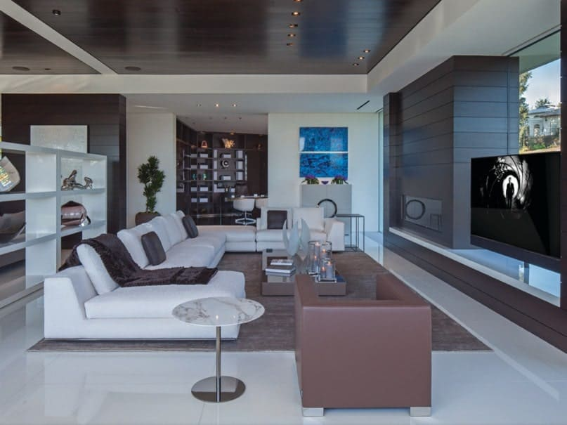 A contemporary living room featuring a large white sofa set and a large area rug along with a large widescreen TV in front.