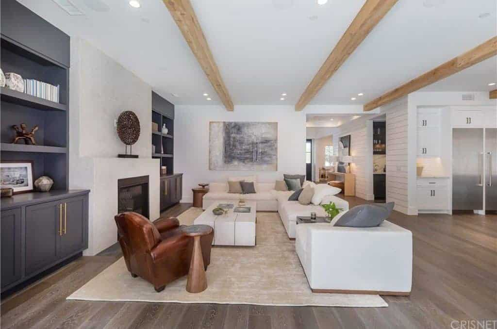 A spacious living area featuring white seats and built-in gray shelving along with a fireplace. The ceiling has exposed beams as well.