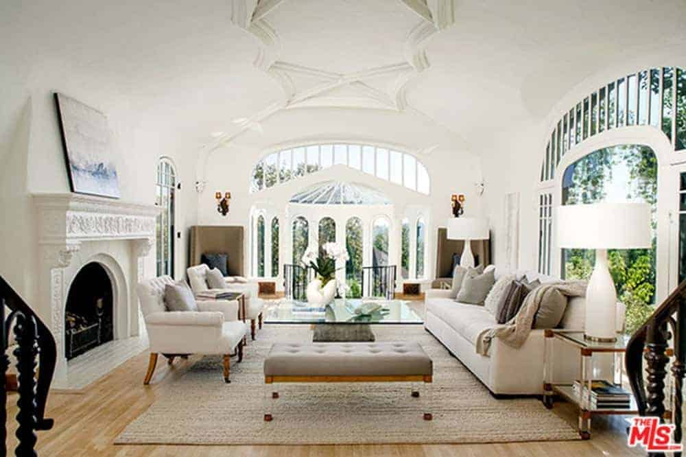 This home boasts a living room with a set of white seats and a glass top center table along with a fireplace under the stunning decorated ceiling.