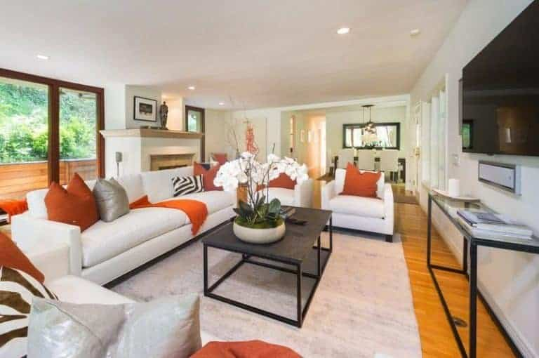 This living room offers a set of white seat with an orange accent along with a large widescreen TV on the wall.