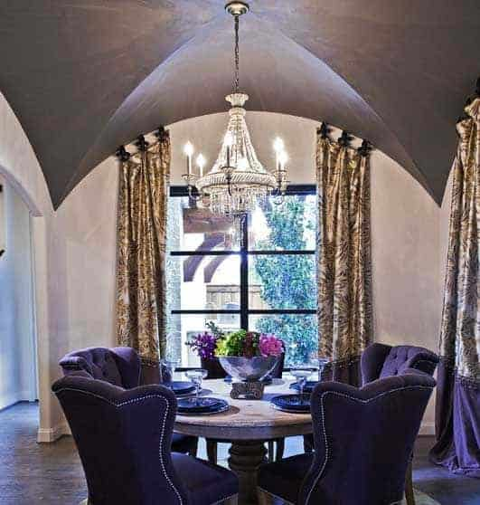 The circular wooden table is encircled with purple velvet cushioned chairs that match with the curtains that has a purple design on its edges complementing the dark hardwood flooring illuminated by the majestic chandelier from the groin arch ceiling.