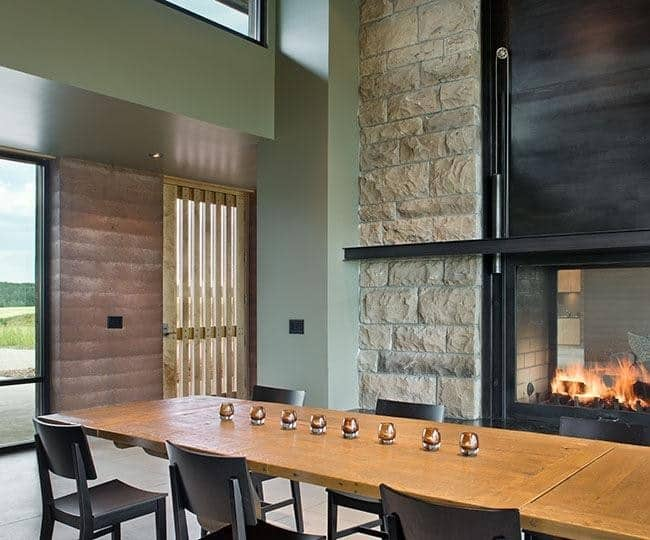 The long rectangular wooden dining table is paired with black wooden chairs that lend with the frame of the fireplace that is fixed against a large pillar of beige stones that stands out beside the light green hue of the walls but matches with the beige flooring tiles.