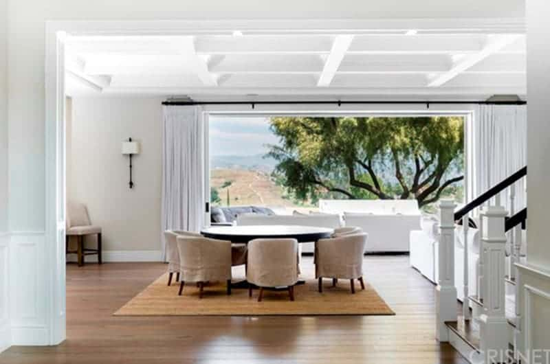 A large and lush tree adorns the landscape featured by the large open wall flanked with white curtains that blend with the white coffered ceiling and beige walls. This is given an earthy contrast with the dark wooden round table and its cushioned chairs with brown slipcovers and a hardwood flooring topped with a light brown area rug.