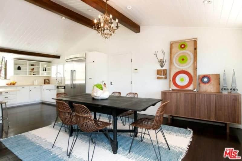 The bright and white ceiling has a couple of wooden exposed beams that matches with the hue of the rustic chairs surrounding the black wooden dining table that stands out against the light hue of the area rug on the dark hardwood flooring.