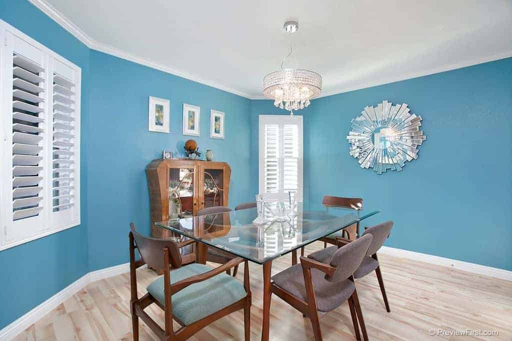 The bright blue walls of this dining room is reminiscent of the blue skies above the beach with the white clouds represented by the white shuttered windows and the sandy beach is the light hardwood flooring that emphasizes the glass-top dining table and its wooden armchairs.