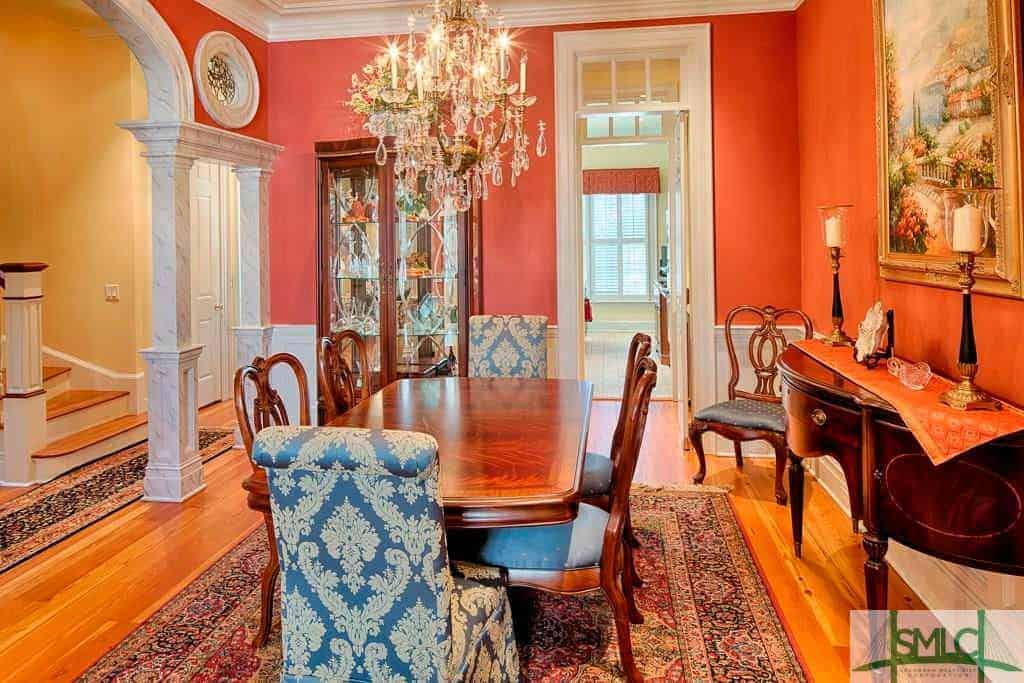 This chic dining room has a majestic crystal chandelier that elevates the elegance of the wooden dining table and its wooden chairs. On each end of this table is a blue patterned cushioned chair that goes well with the colorful patterned area rug and the orange walls.