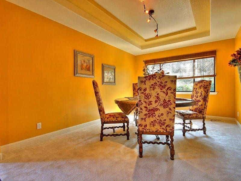 This bright and cheerful shade of orange encloses the dining room with an eye-pleasing quality that elevates the chic patterned chairs surrounding the round wooden table topped with a decorative lighting that looks like flowers on a vine.