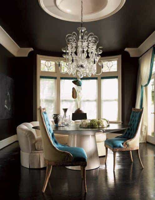 The black hardwood flooring matches with the black walls and ceiling that has a contrasting white circular center dome that supports a white majestic chandelier that perfectly fits the white modern circular glass-top dining table as well as the other white elements that stand out.