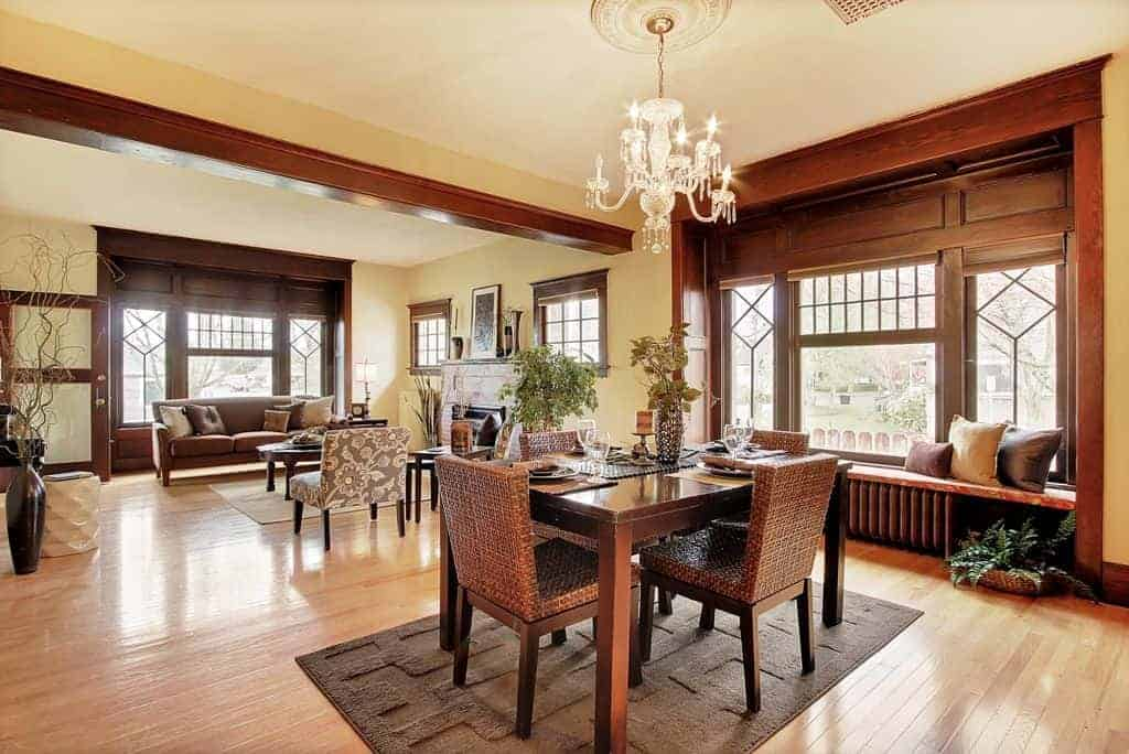 The wooden rectangular table is paired with woven wicker chairs of the same hue over a dark gray area rug of the light hardwood flooring. The table matches with the large wooden wall that houses the windows and a built-in cushioned bench for a sitting nook.