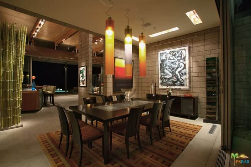 The highlight of this medium-sized dining room is the trio of tube-like pendant lights that have a colorful orange hue to them that stands out against the dark wooden dining set that matches with the console table, area rug and even the stone walls.