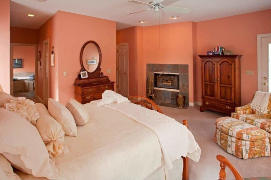 Primary bedroom with orange walls and carpeted flooring. The room offers a comfy bed, a fireplace and its own bathroom.