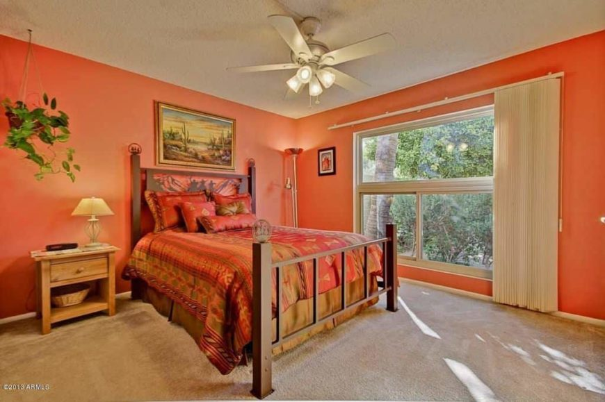 Primary bedroom featuring orange walls and carpeted flooring. The room offers a classy bed with a rustic side table topped by a table lamp on the side.