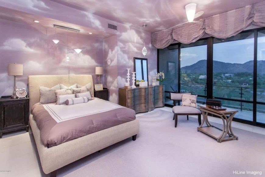Purple primary bedroom boasting purple decorated walls and ceiling. The room also has carpeted flooring and a private balcony area. The room has a nice bed set.