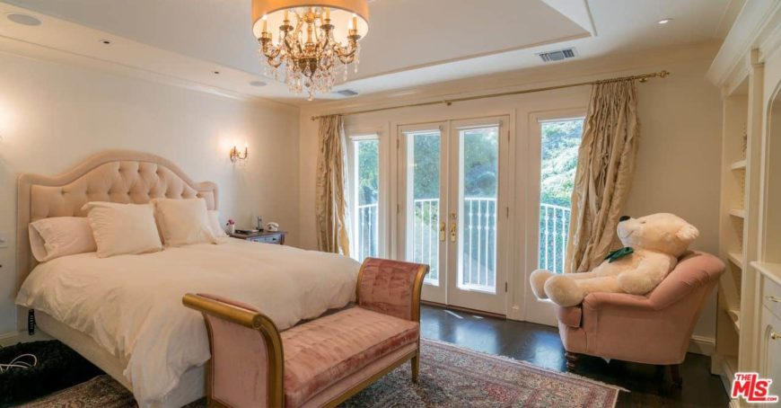 Primary bedroom featuring a nice bed. The room is lighted by a gorgeous chandelier. The room also has a private balcony area.