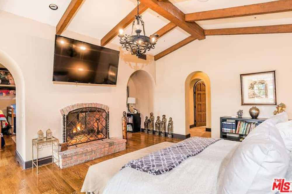 Mediterranean primary bedroom with hardwood flooring and a ceiling with beams. The room offers a large widescreen TV just above the room's fireplace.