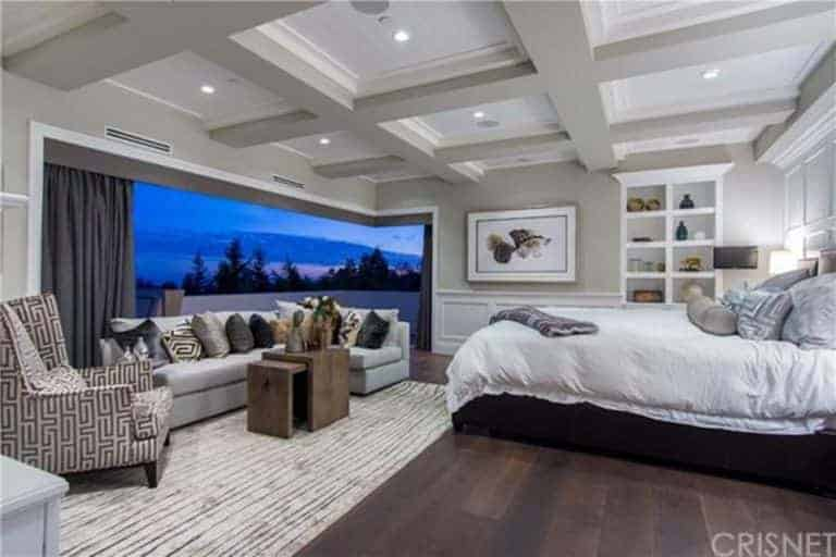 Primary bedroom with a classy coffered ceiling and hardwood flooring. There's a living space featuring an L-shaped couch in front of the bed.