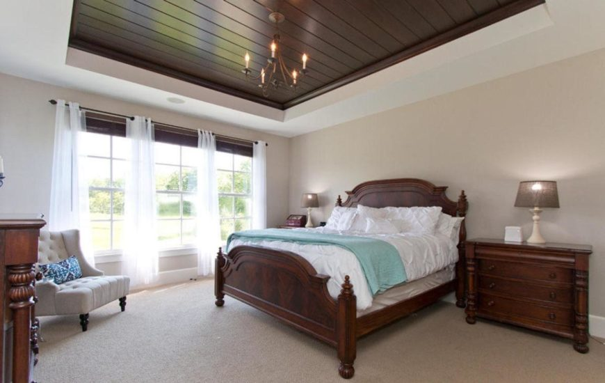 Primary bedroom featuring a tray ceiling and carpeted flooring. It offers a classy bed with two side tables, both have table lamps on top.