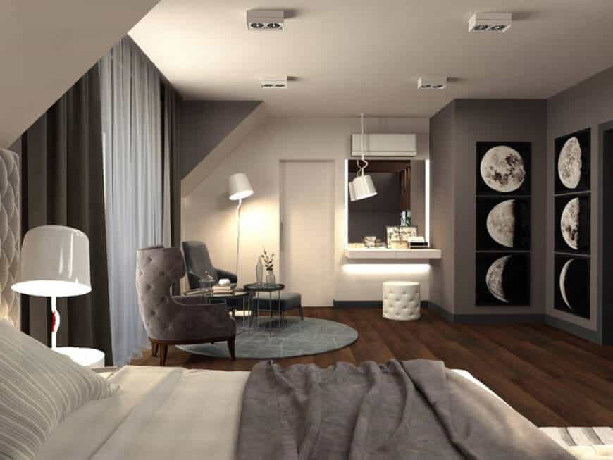 A primary bedroom with photographs of the Moon on its walls. It has a floating vanity and a small living space lighted by stylish lighting.
