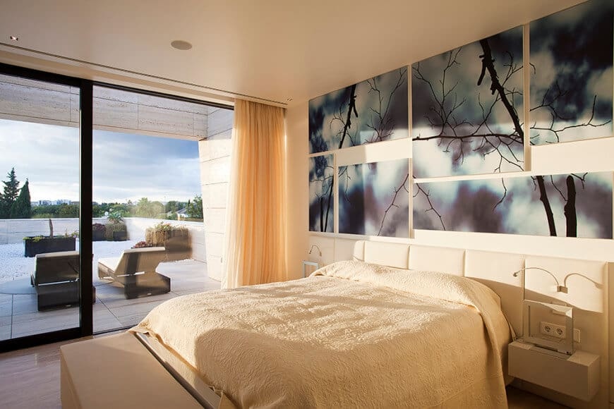 Primary bedroom featuring artistic wall decors. The room has a sliding glass doorway leading to the home's large balcony.