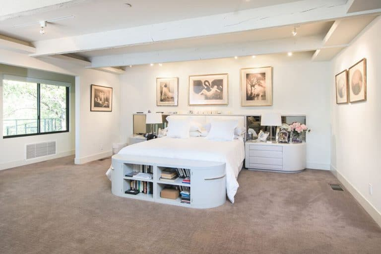 Spacious primary bedroom with gray carpet flooring and white walls with multiple wall decors. The bed frame features built-in shelving. The room also offers two bed side tables both with table lamps.