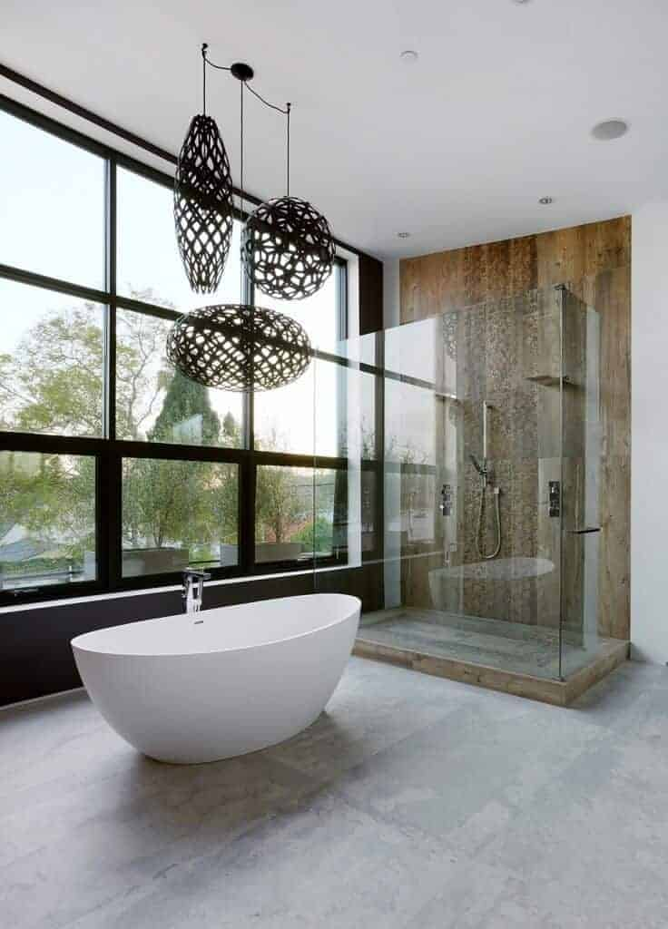 This modern bathroom has a high white ceiling complemented by the large glass window with black frames matching the pendant lights with artistic covers hanging over the white freestanding tub beside the glass enclosed shower area.