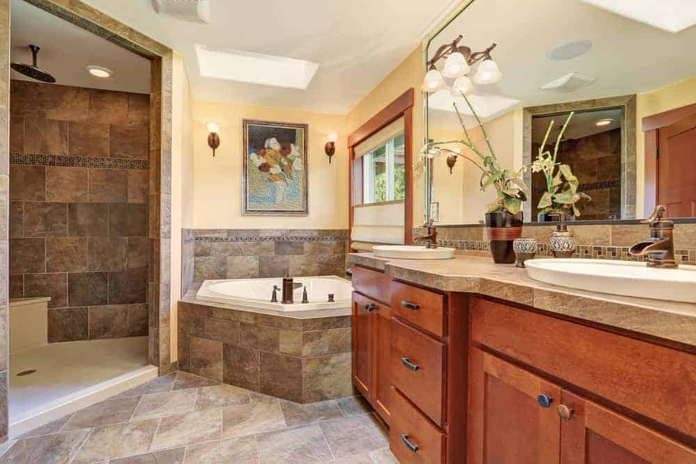 The brown marble countertop of the two-sink wooden vanity matches with brown marble flooring and bathtub housing at the corner with a beautiful flower painting mounted on the yellow wall above it brightened by a white ceiling.