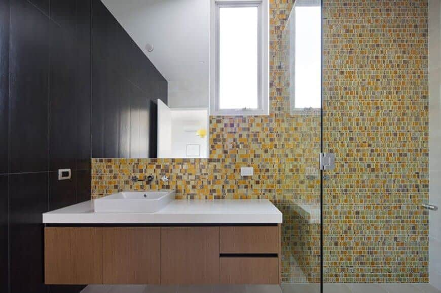 The walls of this lovely bathroom are filled with colorful small tiles mostly yellow to give a complex background for the floating wooden vanity with a plain white countertop and sink contrasted by the black adjacent wall.