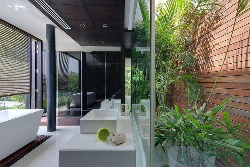 The white flooring matches with the white bathtub and sinks of the white stone vanity. This is contrasted by the black ceiling and pillar that is complemented by the wooden fence right outside the glass walls.