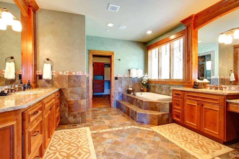 The white ceiling is complemented by the upper section of the walls that have a greenish hue. This is perfectly paired with brown marble tiles of the lower walls and the flooring making the wooden elements of the vanities stand out.