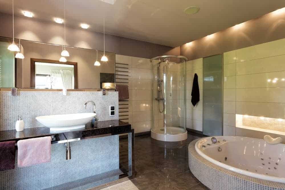 The brilliant white ceiling has recessed lights that illuminate the gray upper walls that contrast the white tiles of the walls. This makes the dark floor tiles stand out with the bathtub inlaid in gray tiles same as the sink area.