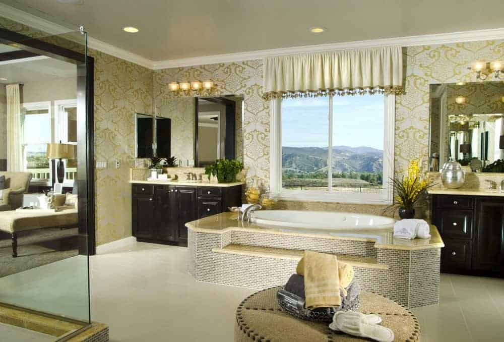 The walls of this lovely bathroom is dominated by a wallpaper with elegant yellow patterns on a light gray background that matches with the gray tiles of the bathtub that has the same beige countertop as the two black wooden vanities.