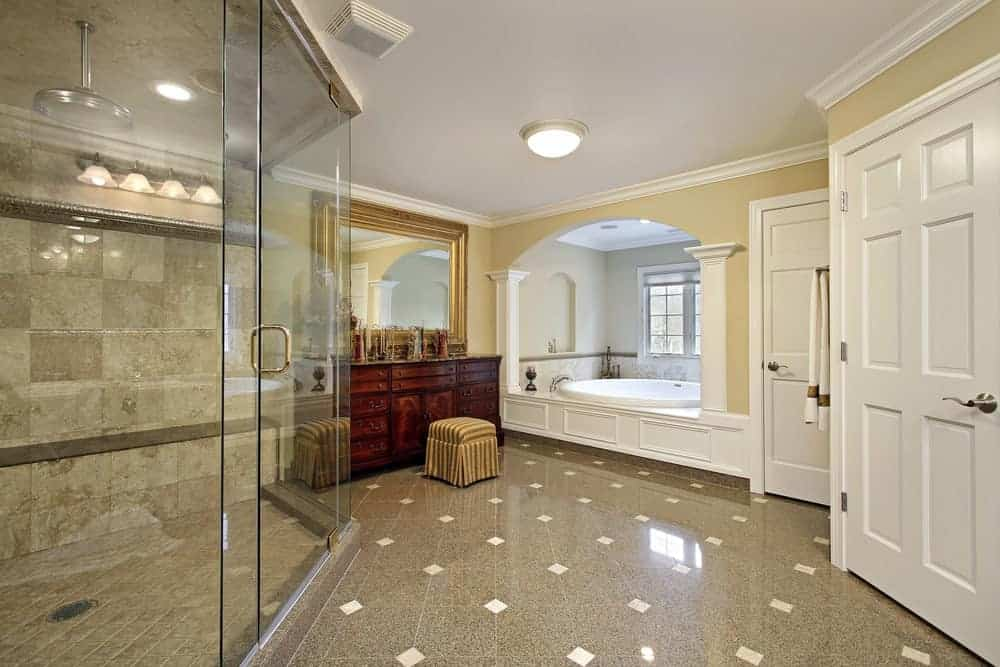 The delightful yellow walls are a nice complement to the white ceiling and white housing of the bathtub that is placed in a window alcove. Across from this is the glass enclosed shower area that has gray tiles complementing the flooring.