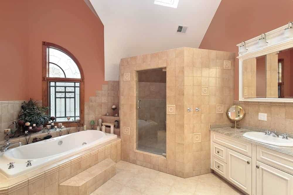 The salmon pink tiles of the flooring and lower part of the walls extend to the structures housing the shower area and bathtub across from the white vanity with a white mirror that stands out against the upper walls that have a burnt sienna hue.