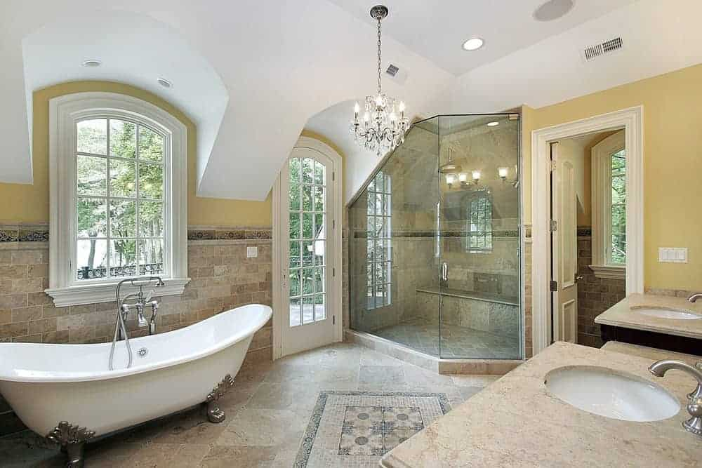 The uneven white arched ceiling of this bathroom stands in contrast with the yellow walls complemented by various beige marble tiles serving as a wainscoting matching with the flooring. This makes the white freestanding bathtub stand out.