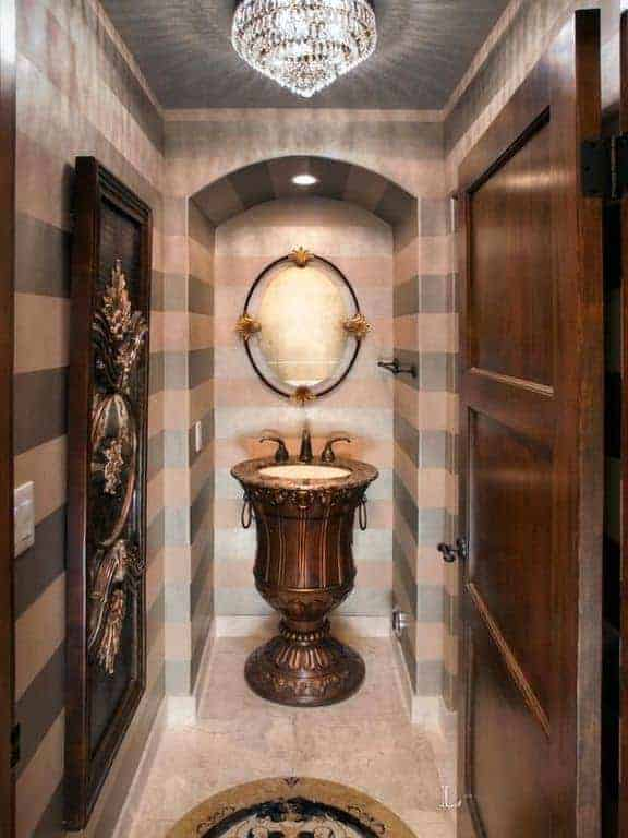 This elegant bathroom has white circular sink inlaid with a rose gold structure that is shaped like a goblet with intricate carvings on the side matching the large embossed wall-mounted artwork on the adjacent wall that has a striped design.