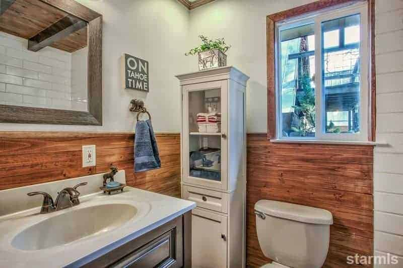 This small and simple bathroom has gray upper walls paired with a redwood wainscoting that puts emphasis on the light gray thin cabinet, toilet and countertop of the dark wooden vanity with an elegant brass faucet.
