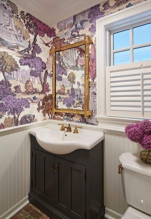 This chic bathroom is dominated by colorful safari designs on the wallpaper above the white wainscoting that puts emphasis on the black wooden cabinets of the small vanity with a white sink on it beside the white toilet.