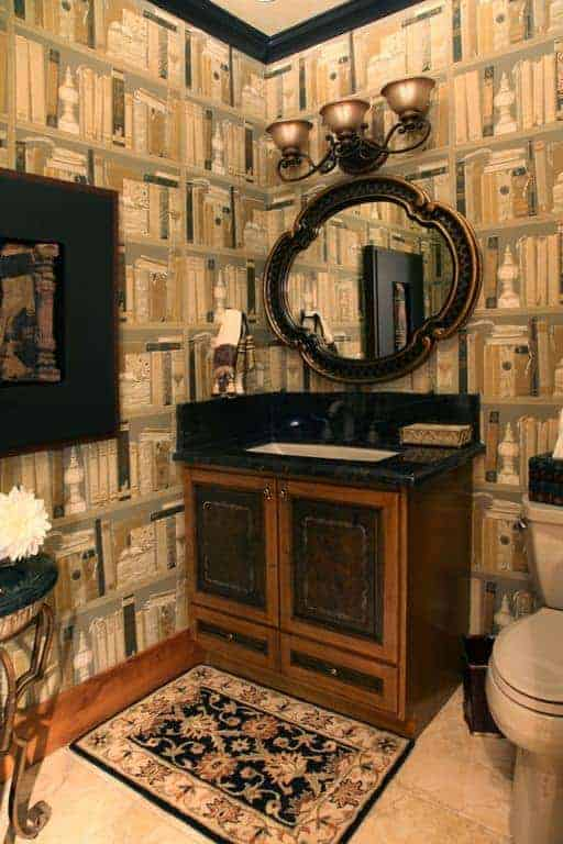 The elegant wallpaper of this bathroom has designs on it depicting bookshelves filled with books. This is a charming background that provides a sense of complexity to the wooden vanity and the porcelain toilet beside it.