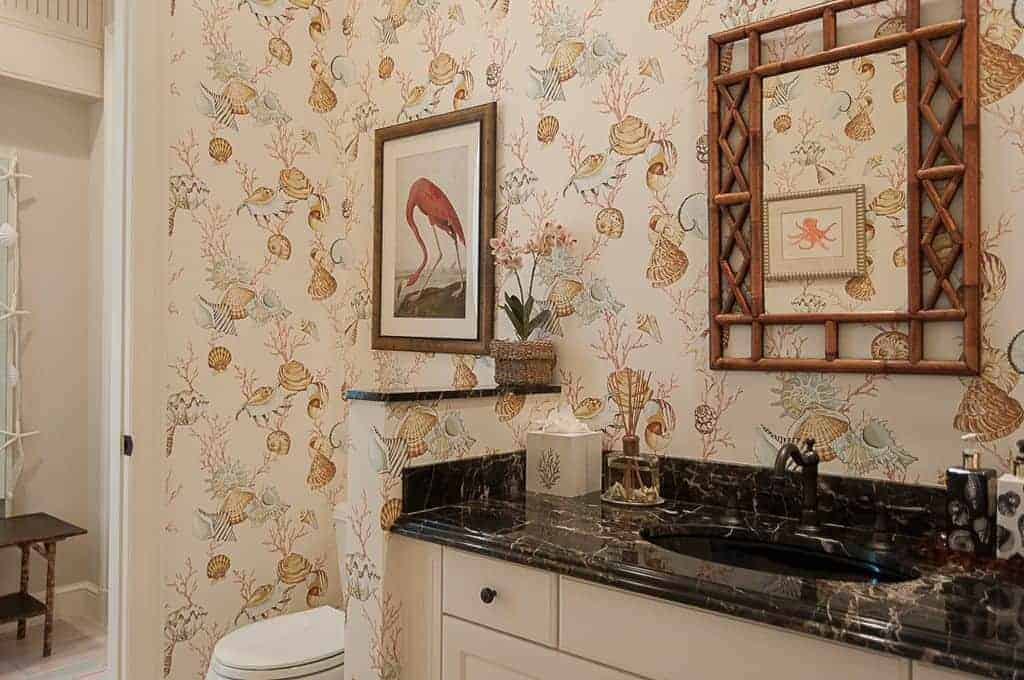 The charming and chic wallpaper on the walls are filled with colorful depictions of shells providing a charming background for the wall-mounted artwork above the white toilet beside the bamboo-framed mirror of the black countertop of the sink.