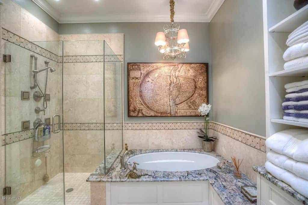 The avocado green wall above the circular corner bathtub is adorned with a beautiful artwork that is augmented by a small elegant chandelier illuminating the beige backsplash that extends to the glass-enclosed shower area with beautiful fixtures.
