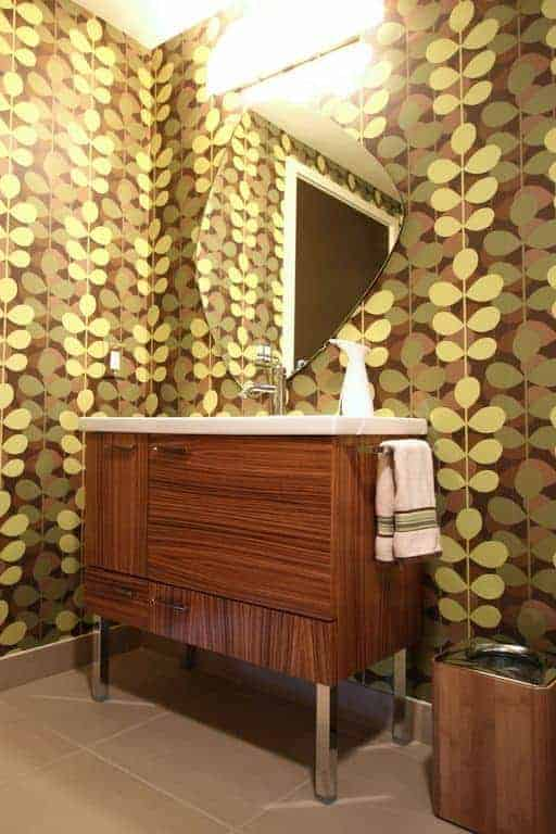 The small vanity of this simple bathroom has wooden cabinets and drawers matching with the trashcan beside it that stands out against the brilliant green wallpaper with designs of vines and leaves on it illuminated by the wall-mounted lamp above the mirror.