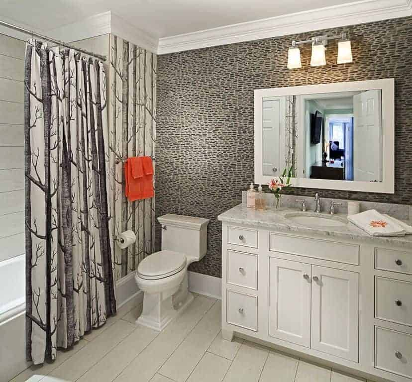 The classic white cabinets and drawers of the white vanity that stands out against the complex gray wallpaper matches with the toilet beside as well as the bathtub that is covered with a black and white patterned shower curtain.
