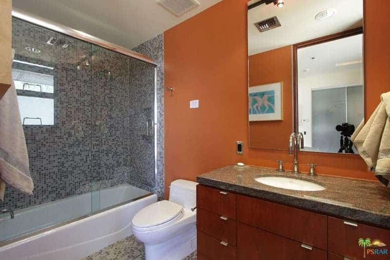 The frameless vanity mirror is mounted on a wall with a burnt sienna hue that contrasts the white porcelain toilet beside the glass enclosed shower area filled with small gray tiles that give a complex background matching the flooring.