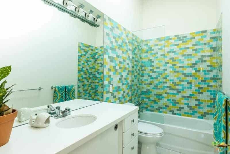 The bathtub area that also doubles as the shower area is dominated by colorful tiles of yellow, gray and green hues providing a nice colorful background for the white toilet and white vanity with a white countertop with a small white sink.