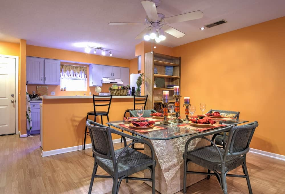 The simple and rustic gray bamboo chairs of the glass-top dining table are elevated to a whole new level with the orange background that provides a delightful contrast for the eyes allowing for a unique aesthetic that pairs well with the hardwood flooring.