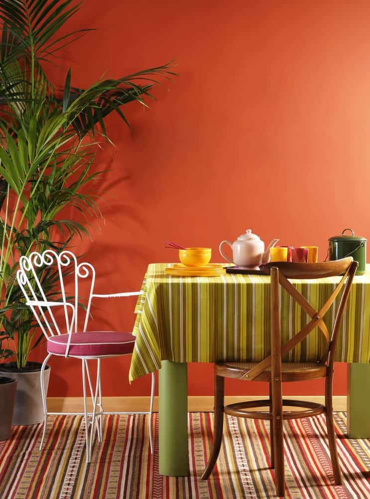 The earthy shade of orange that dominates the wall is a perfect pair for the colorful elements of this dining area like the colorful area rug and the green striped table cloth. The earthy shade brings them all back to earth and binds them.